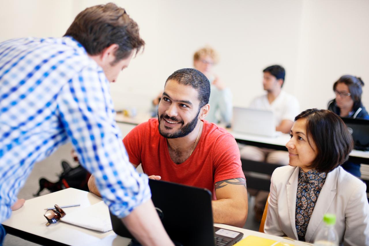 Studierende im Gespräch mit einem Dozenten