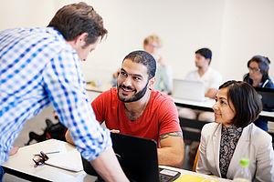 Lehrbeauftragter im Gespräch mit zwei Studierenden