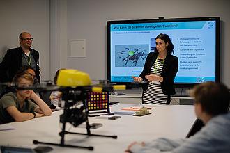 Wissenschaftlerin bei einem Vortrag über eine Drohne