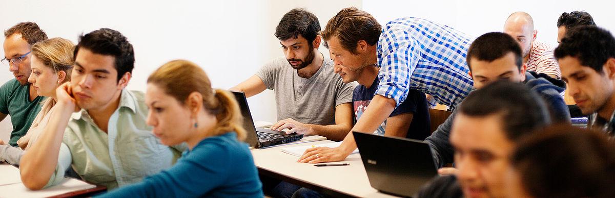 Dozent erklärt Studierenden etwas am Computer